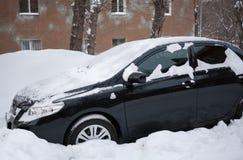 用雪盖的黑汽车站立在随风飘飞的雪在房子附近 库存图片