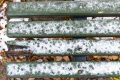 用雪盖的绿色板条 免版税库存照片
