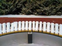 用雪盖的黄色长凳 图库摄影