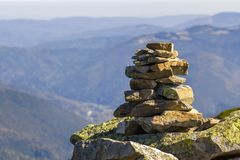 用青苔盖的堆石头在山背景的一座山顶部 平衡和和谐的概念 堆禅宗岩石 库存图片