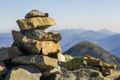 用青苔盖的堆石头在山背景的一座山顶部 平衡和和谐的概念 堆禅宗岩石 免版税库存照片