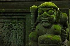 用青苔盖的巴厘语石雕象 免版税图库摄影