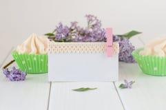 用鞋带磁带装饰的空的卡片在蛋白甜饼蛋糕和bouqu附近 免版税库存图片