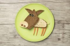用食品成分做的滑稽的猪在板材 免版税库存照片
