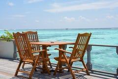 用餐与木桌和椅子的设定在海洋附近的餐馆 库存图片