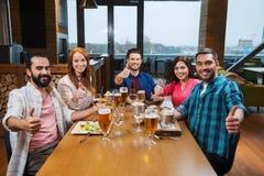 用餐和喝啤酒的朋友在餐馆 免版税图库摄影