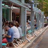 用餐在一个边路咖啡馆的人们在城市 免版税库存照片
