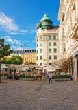 用餐在咖啡馆莫扎特维也纳街道大阳台的人们  库存图片