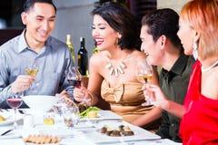 用餐在花梢餐馆的亚裔朋友 免版税库存照片