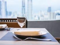 用餐在表上的集合在餐馆有城市地平线视图 免版税库存图片