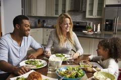 用餐在他们的厨房里的女孩和她的混合的族种父母 库存图片