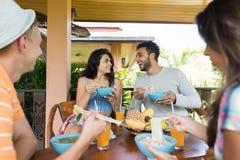 用餐的人们一起吃与筷子愉快的微笑的年轻人和妇女的亚洲面条享用传统亚洲 免版税库存图片