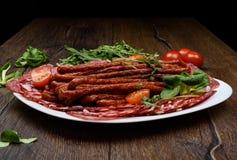 用香肠的不同的类型的一块板材在一张木桌上的 图库摄影