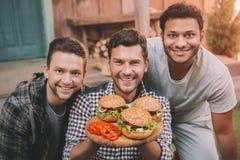 用鲜美汉堡微笑对照相机的愉快的年轻人 库存照片