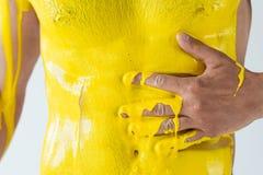 用黄色油漆报道的男性身体播种的看法 库存照片