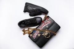 用黑闪闪发光星和与用发光的星装饰的金链子的一个黑袋子装饰的黑运动鞋,衣服饰物之小金属片 免版税库存照片