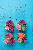 用从五颜六色的甜点的花装饰的美丽的杯形蛋糕 库存图片