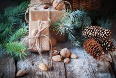 用绳子装饰的圣诞节礼物箱子,具球果,杉木锥体,核桃,在木背景的杏仁 免版税库存照片
