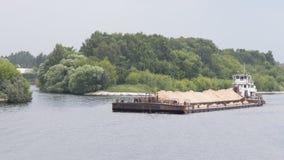 用黄沙浮游物装载的驳船 免版税库存图片