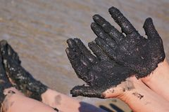 用黑医治用的泥和脚包括的妇女手,含沙海滨在背景中 免版税库存照片