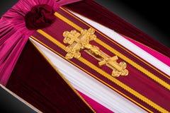 用紫色和白色布料盖的闭合的棺材装饰用教会在灰色豪华背景的金十字架 特写镜头 免版税库存图片