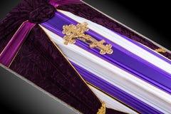 用紫色和白色布料盖的闭合的棺材装饰用教会在灰色豪华背景的金十字架 特写镜头 库存照片