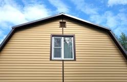 用黄色房屋板壁和棕色金属屋顶正面图盖的一部分的农村房子墙壁 免版税库存图片