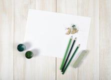 用绿色树胶水彩画颜料瓶子、色的铅笔、白垩、削片和白皮书装备的设计师工作场所顶视图 免版税图库摄影
