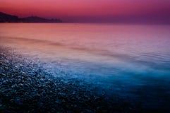 用Pebblestones盖的日落海岸线 库存图片
