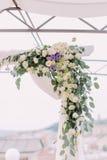 用shite和紫色花的婚礼曲拱可爱装饰的部分 免版税库存图片