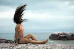 甩她的在岩石的妇女头发在Bakovern海滩,开普敦的日落 图库摄影