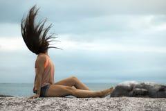 甩她的在岩石的妇女头发在Bakovern海滩,开普敦的日落 免版税库存图片