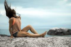 甩她的在岩石的妇女头发在Bakovern海滩,开普敦的日落 免版税库存照片