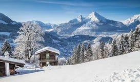 田园诗冬天风景在有山小屋的阿尔卑斯 免版税库存图片