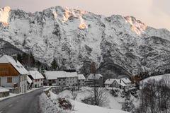 田园诗高山多雪的山口路通过日落天空的,朱利安阿尔卑斯山,斯洛文尼亚村庄 免版税库存照片