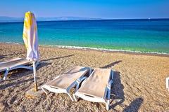 田园诗绿松石海滩遮阳伞和轻便折叠躺椅 图库摄影