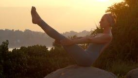田径服的女孩做小船在岩石慢动作的瑜伽姿势 股票视频
