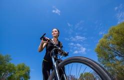 黑田径服的女孩运动员早晨骑一辆自行车在公园 免版税库存照片