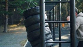 田径服的活跃年轻人做着在公园拳击的体育与在单独消遣区域训练的轮胎 健康 影视素材