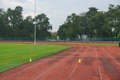 田径运动与2黄色锥体在轨道与人为草在体育场里面 免版税库存图片