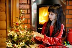 由一个壁炉的儿童女孩在圣诞节 免版税库存照片