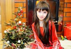 由一个壁炉的儿童女孩在圣诞节 免版税库存图片