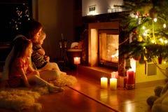 由一个壁炉的愉快的家庭在圣诞节 免版税库存图片