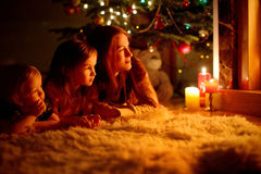 由一个壁炉的愉快的家庭在圣诞节 图库摄影