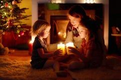 由一个壁炉的愉快的家庭在圣诞节 免版税库存照片
