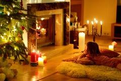 由一个壁炉的愉快的小女孩在圣诞节 免版税库存照片