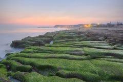 由一个奇怪多岩石的海滩的日出与剧烈的破晓的天空 图库摄影