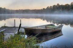 由一个木码头的一条肮脏的小船 免版税图库摄影