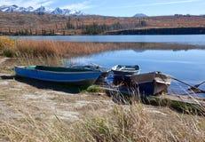 由一个湖的四条小船有山的 库存照片