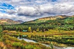 由一个湖的田园诗原木小屋在Aut期间的阿拉斯加的原野 免版税库存图片